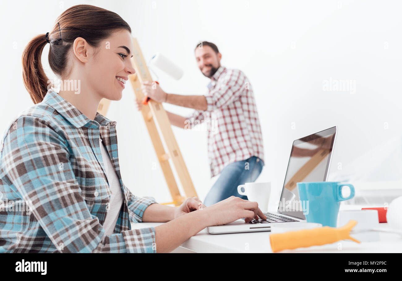 Young smiling couple renovating and remodeling their new apartment, the man is painting the walls with a roller and the woman is connecting with a lap - Stock Image