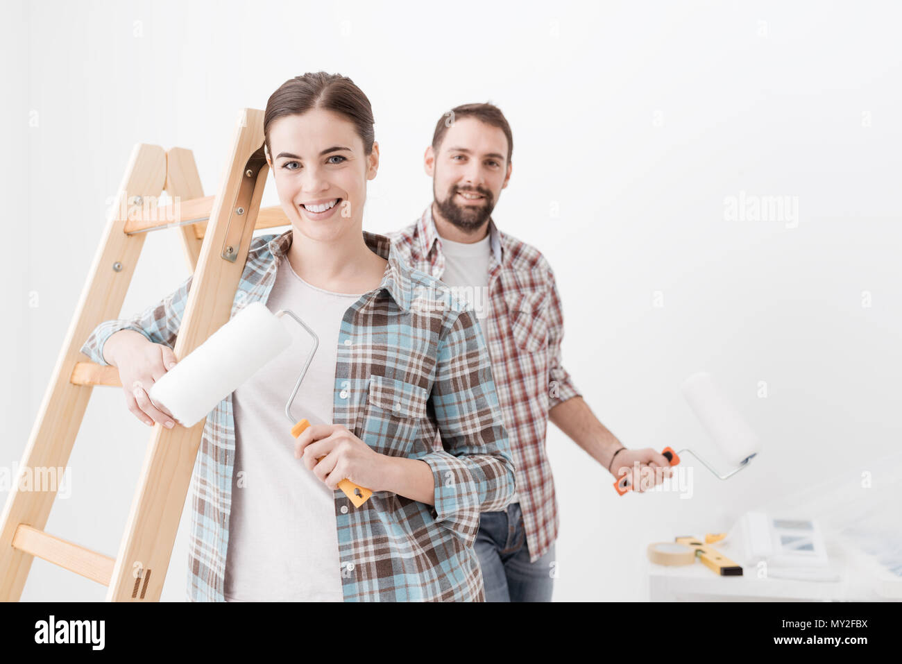 Happy young couple painting their new home, they are smiling and holding paint rollers - Stock Image