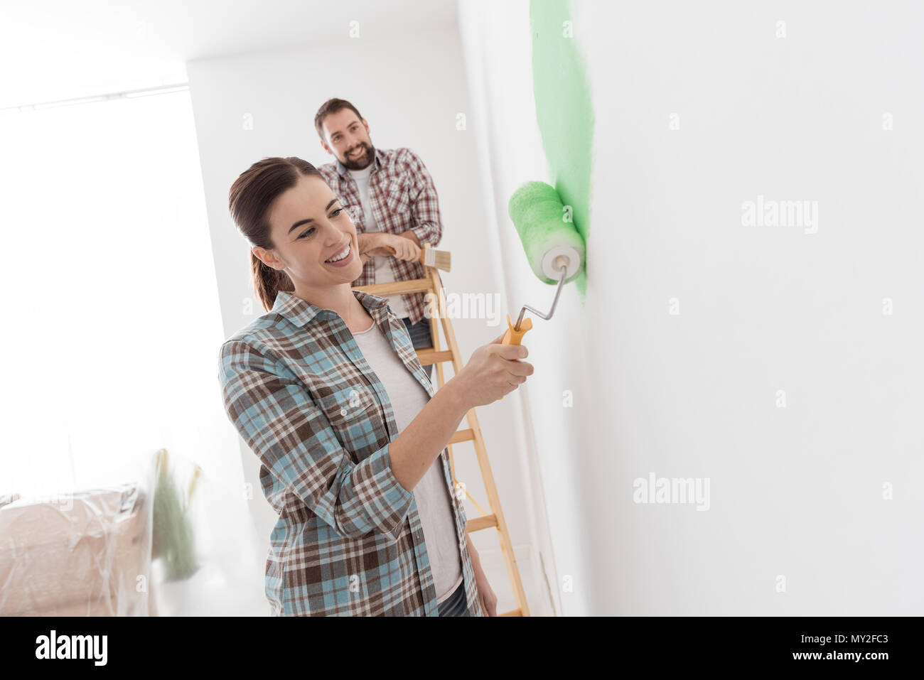 Young cheerful couple renovating their new house, the woman is painting with a paint roller and her boyfriend is looking at her - Stock Image