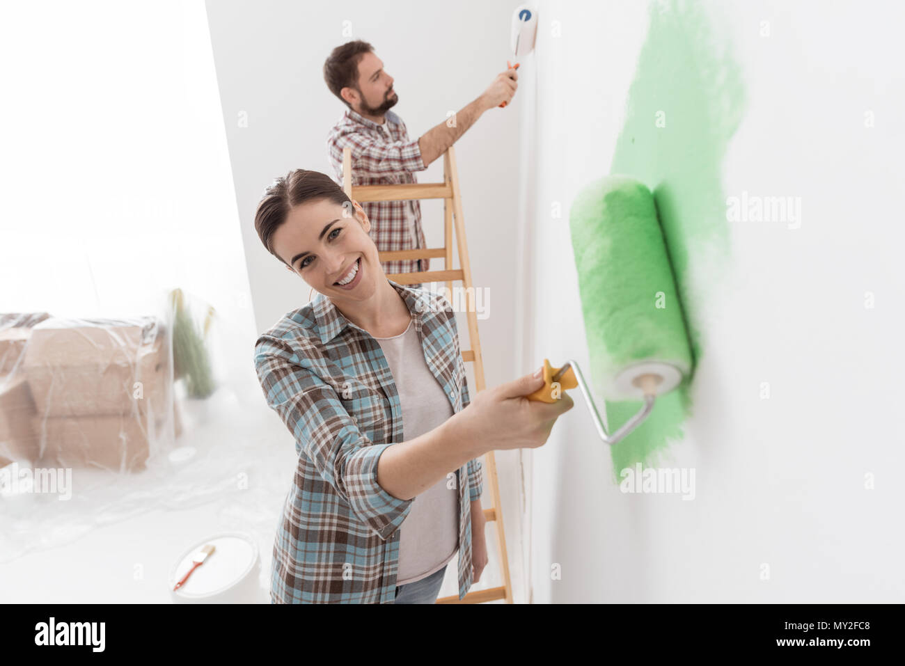 Happy couple painting walls in their new house: the man is standing on a ladder and the woman is using a paint roller and applying bright green paint - Stock Image