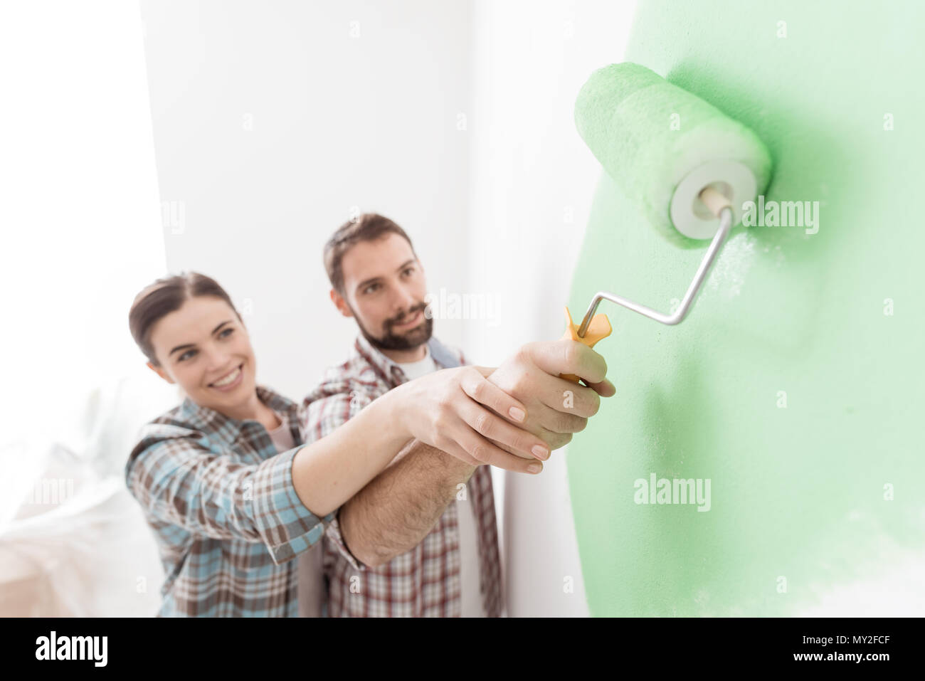 Young loving couple renovating their home, they are painting walls and holding a paint roller together - Stock Image