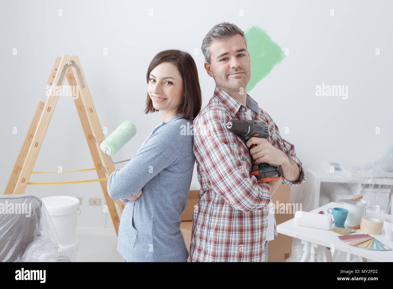 Smiling loving couple doing home renovations, the woman is holding a paint roller and the man is using a drill - Stock Image