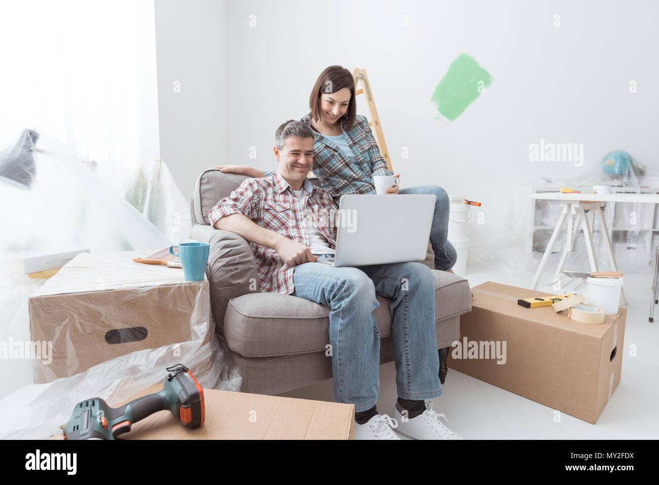 Happy couple moving into a new house and doing renovations, they are having a coffee break and connecting with a laptop - Stock Image