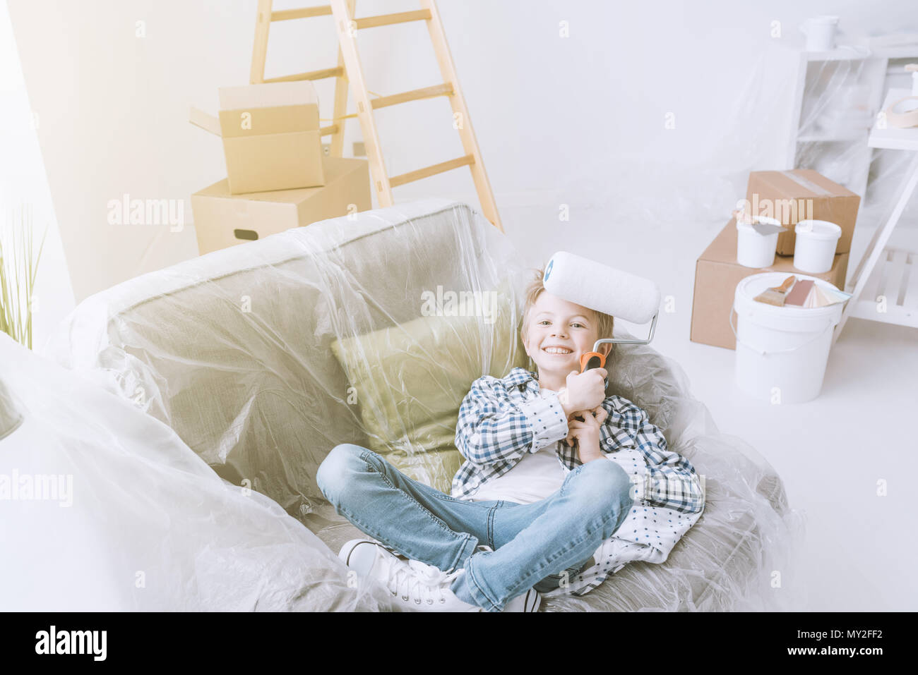 Boy sitting on an armchair covered with a protective plastic sheet and holding a paint roller, home improvement and renovation concept - Stock Image