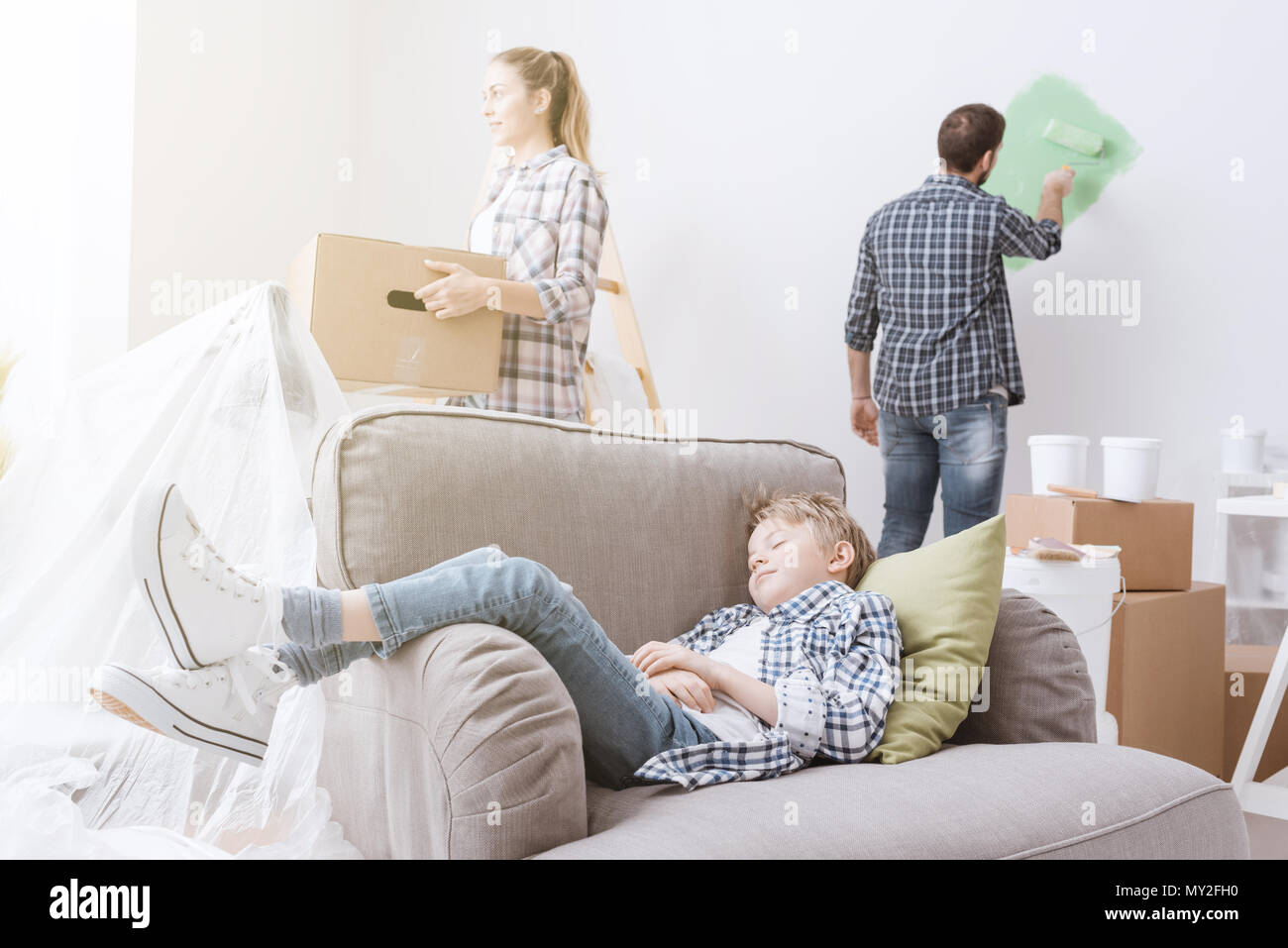 Young family moving into a new house, the mother is carrying a box, the father is painting the room and the child is sleeping on the armchair - Stock Image
