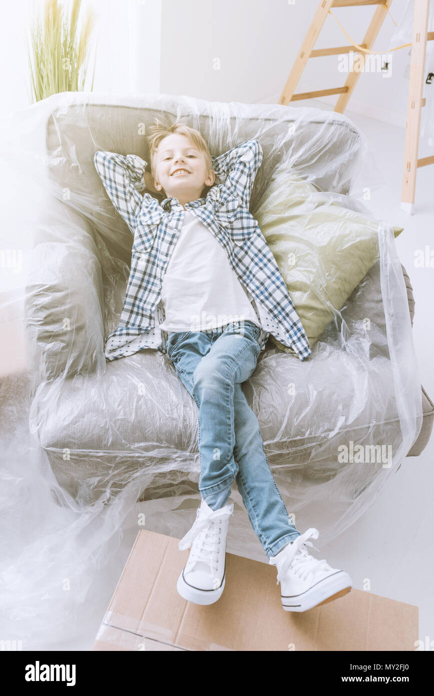 Smiling happy boy relaxing on an armchair covered with a protective plastic sheet, home renovation and relocation concept - Stock Image