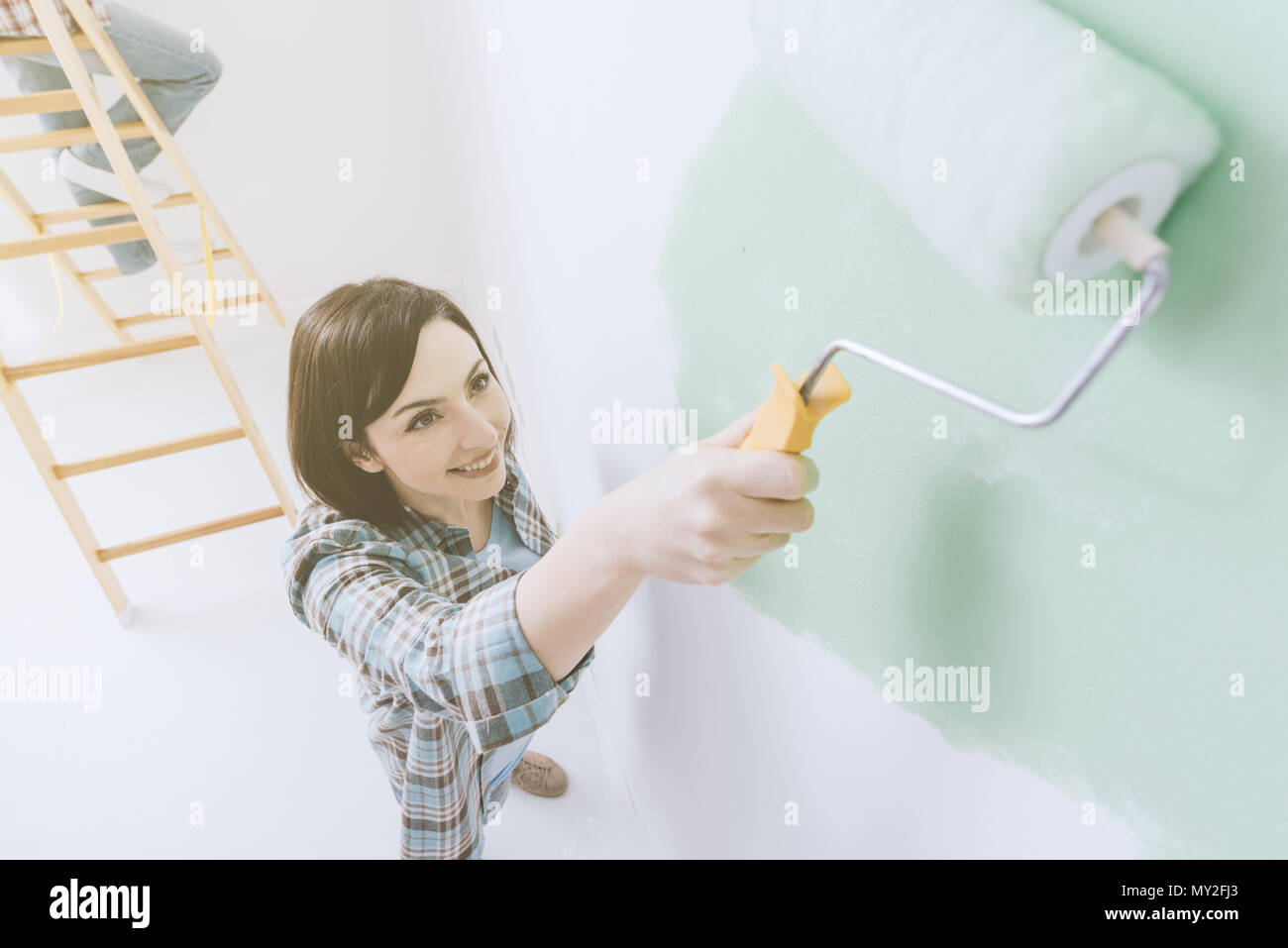 Smiling woman painting a room, she is applying a bright green color using a paint roller - Stock Image