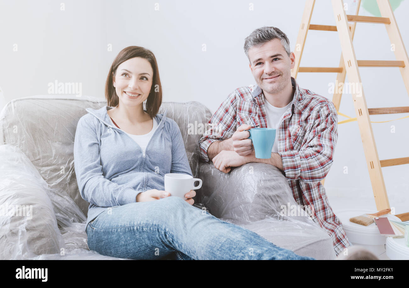 Happy couple doing home renovations in their new house, they are having a coffee break and relaxing - Stock Image