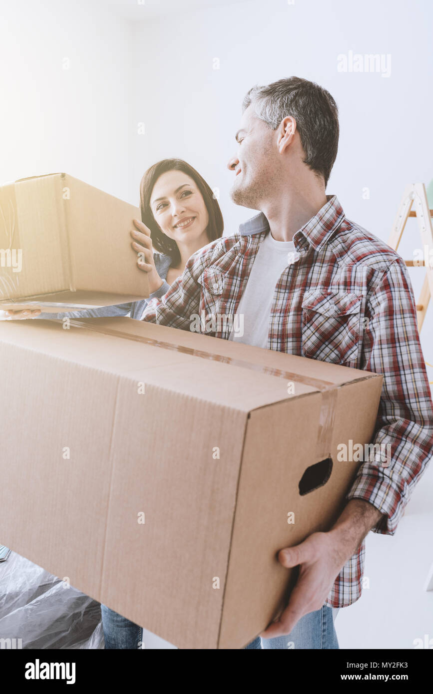 Happy couple moving into a new house and doing home renovations, they are carrying cardboard boxes - Stock Image