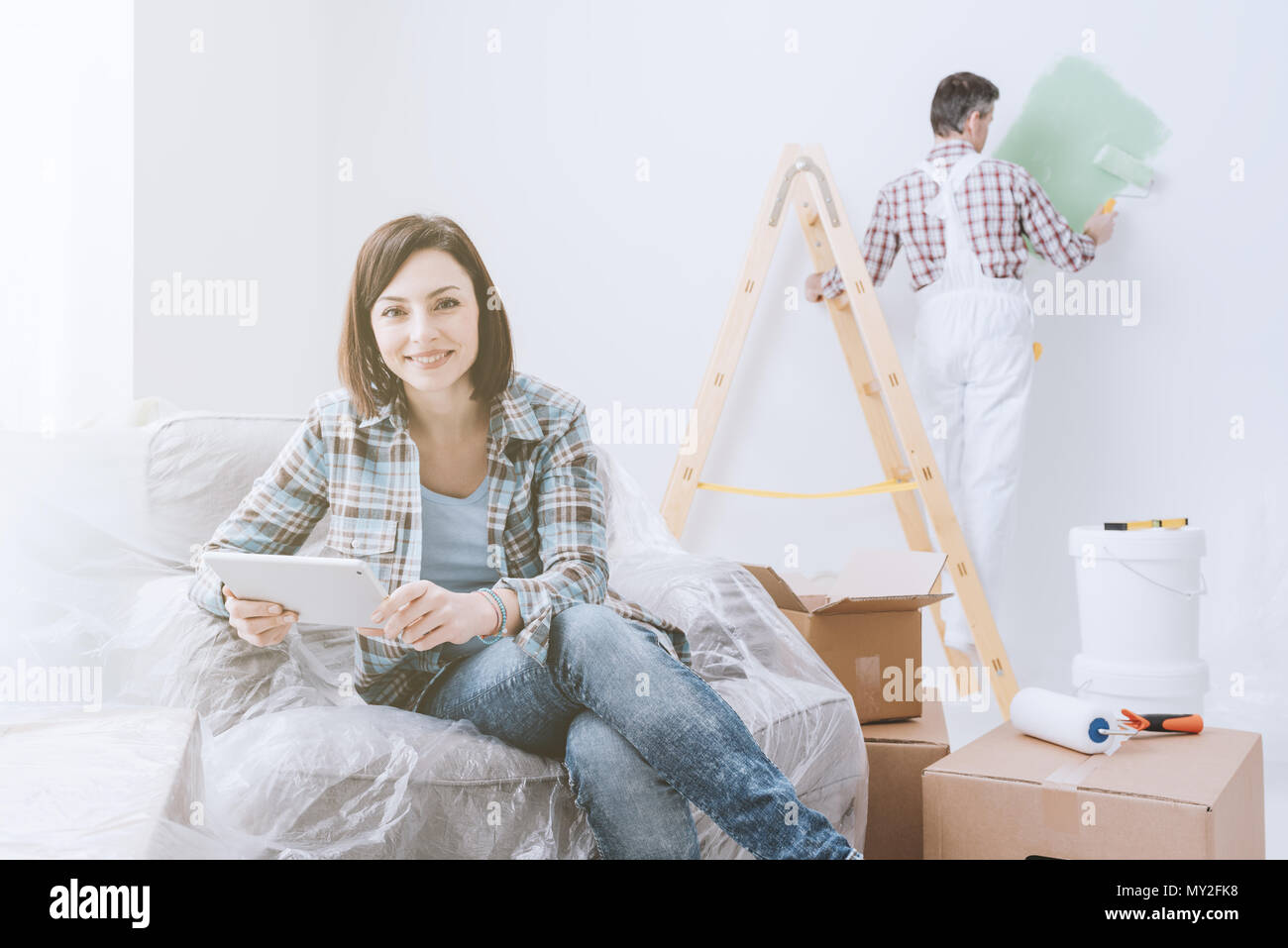 Happy woman relaxing and connecting with her tablet while a painter is painting the room, home renovation concept - Stock Image
