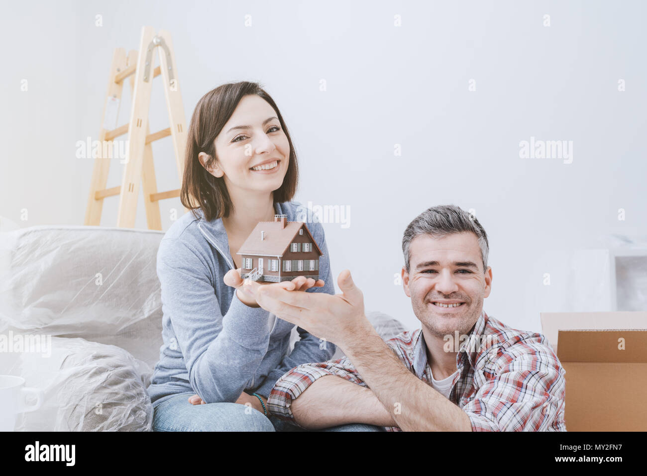 Happy smiling couple holding a model house, they are building their home together, real estate and construction concept - Stock Image