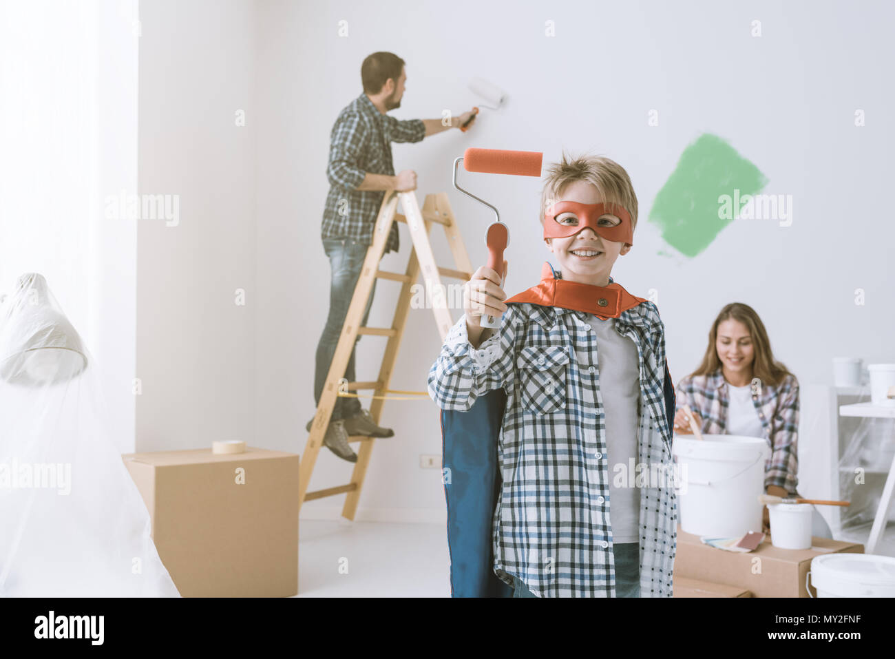 Family renovating their home and painting walls, the boy is wearing a superhero costume and holding a paint roller - Stock Image