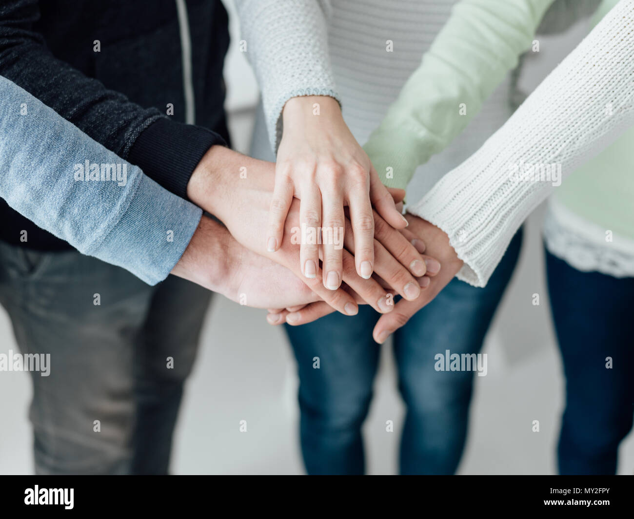 Young people stacking hands together: teamwork, collaboration and support concept - Stock Image