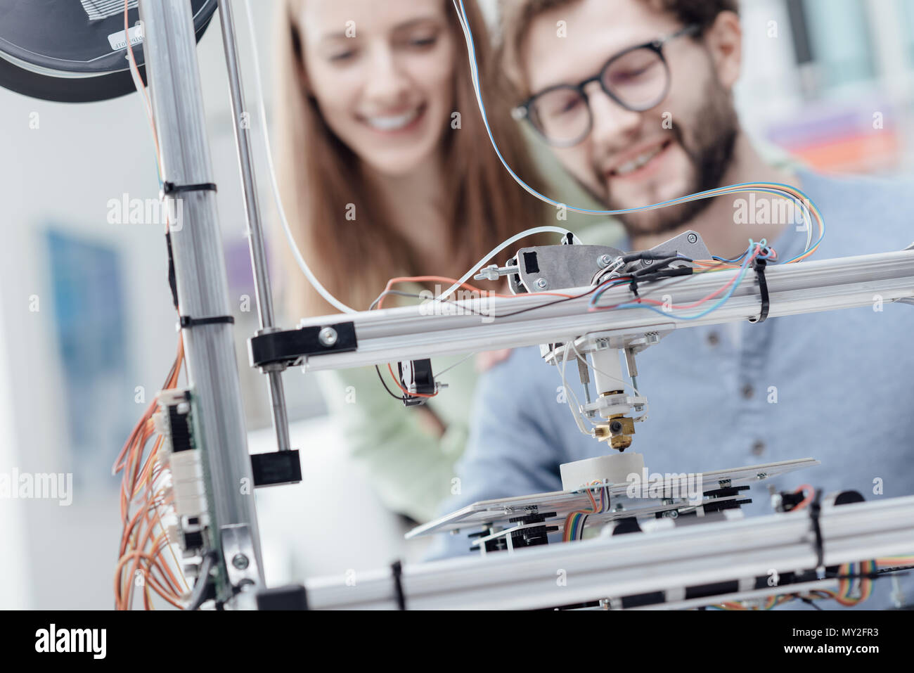 Smiling students using a 3D printer in the school laboratory, they are printing prototypes, technology and learning concept - Stock Image