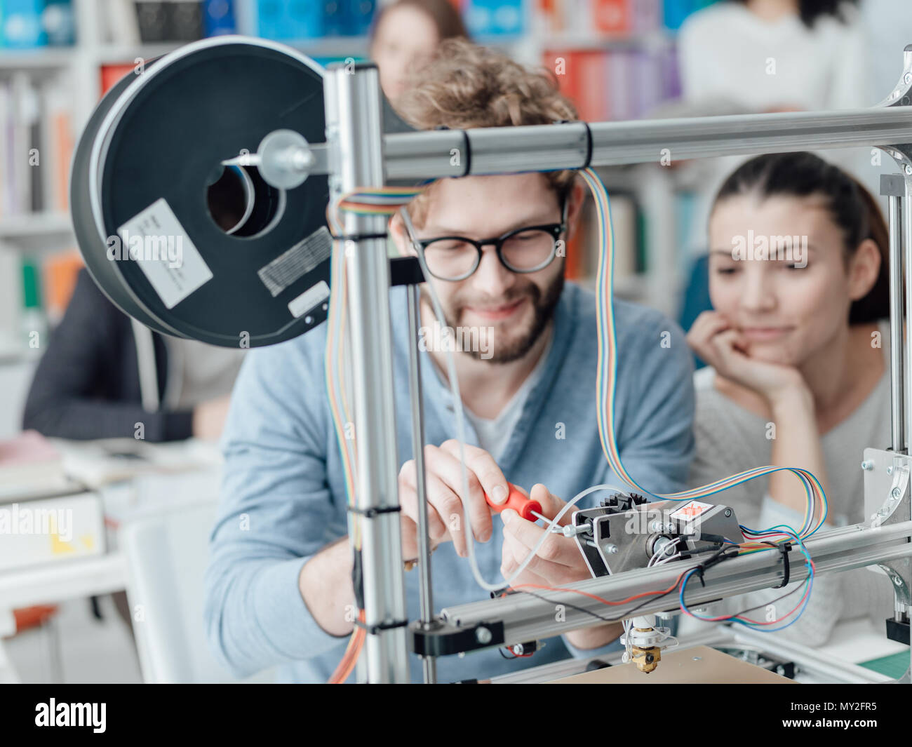 Engineering students using a 3D printer in the laboratory, a student is using a screwdriver - Stock Image