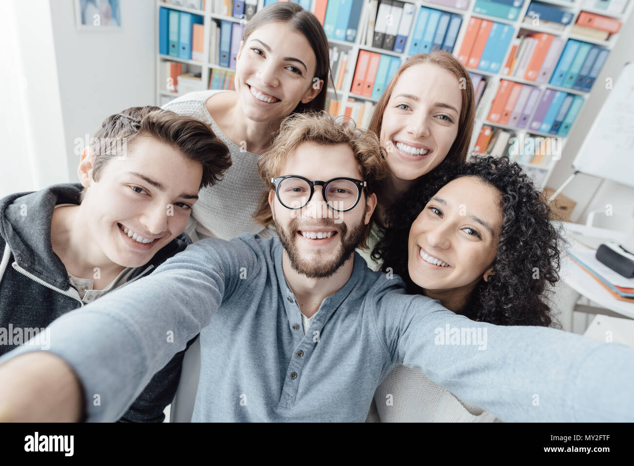 Students taking a selfie together and smiling, togetherness and leisure concept - Stock Image