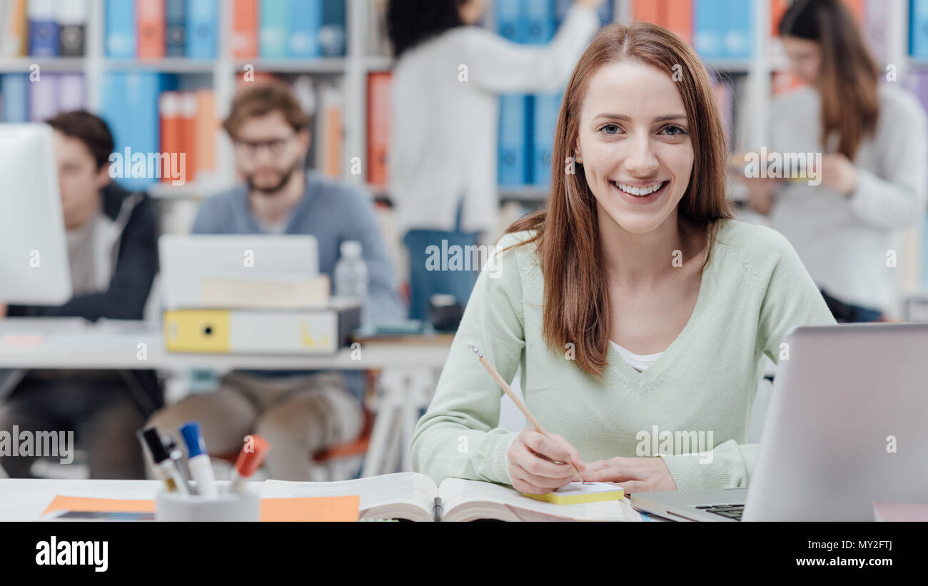 Young smiling female university student sitting at desk and studying a book, group of students on the background, learning and education concept - Stock Image