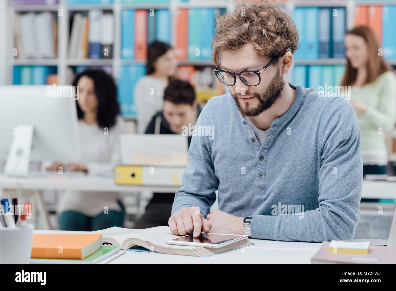 University student sitting at desk and using a digital tablet, group of students in the background - Stock Image