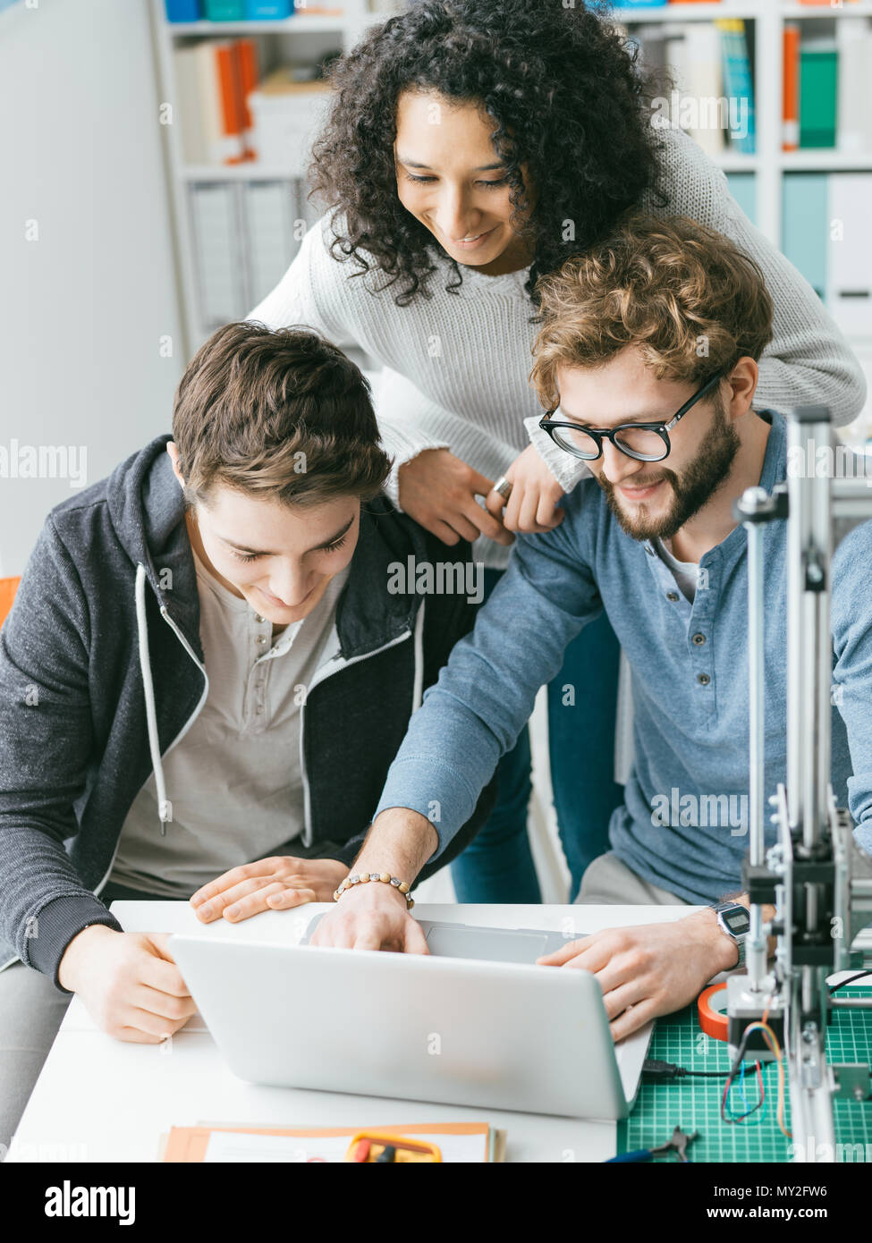 Group of engineering students using a 3D printer and a laptop in the lab, technology and learning concept - Stock Image