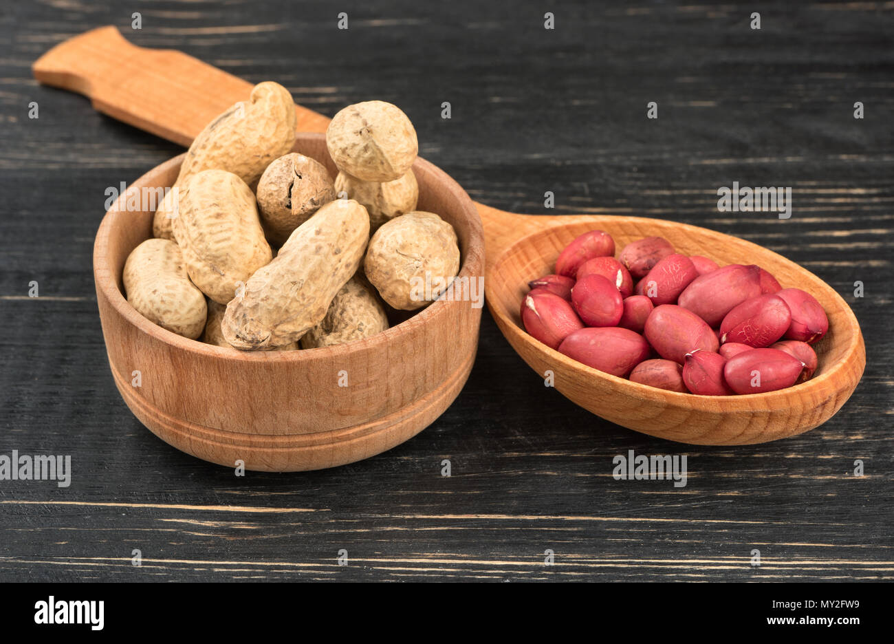 Peanut in a shell in a bowl and cores in a spoon on a wooden background - Stock Image