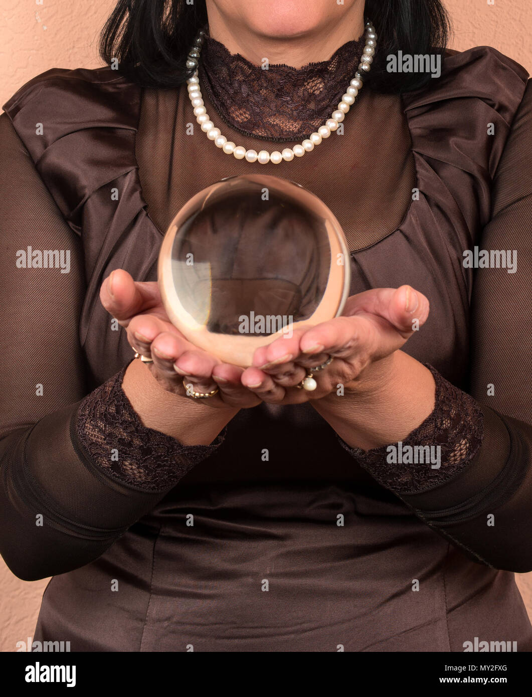 Female fortune teller holding in his hand the magic ball closeup - Stock Image
