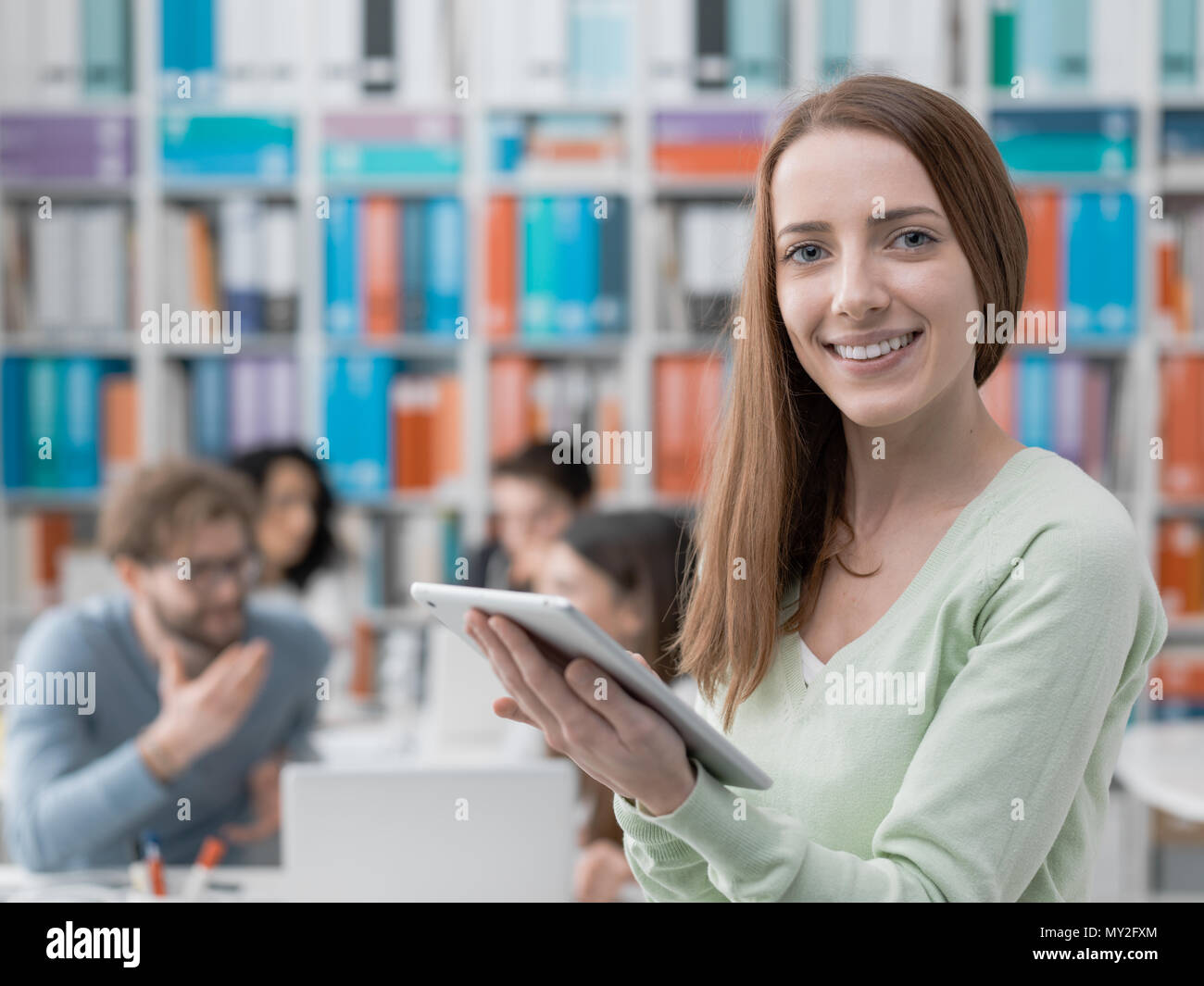 Smiling female student connecting with a digital tablet and group of students in the background - Stock Image