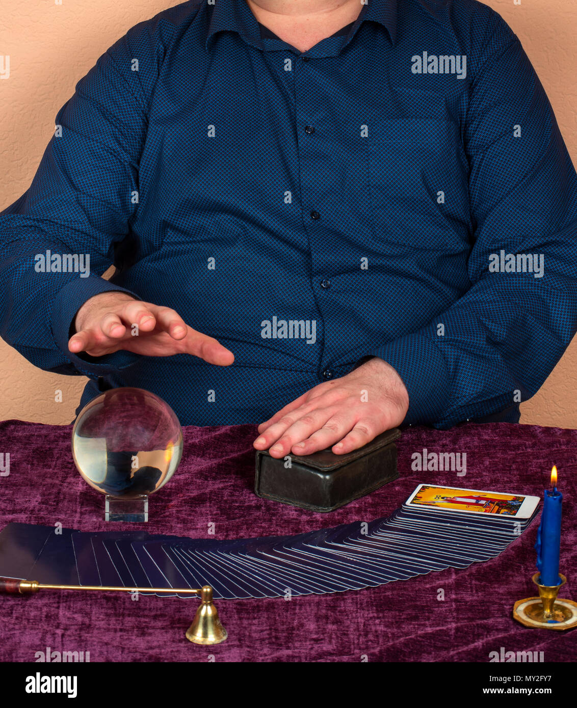 Full man guessing on cards of Taro and the magic ball - Stock Image