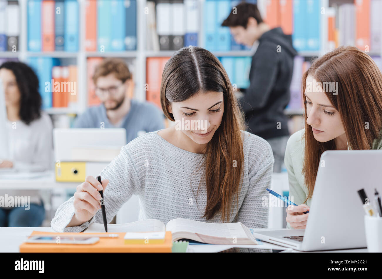 Young female students at the library, they are studying together and reading a book - Stock Image