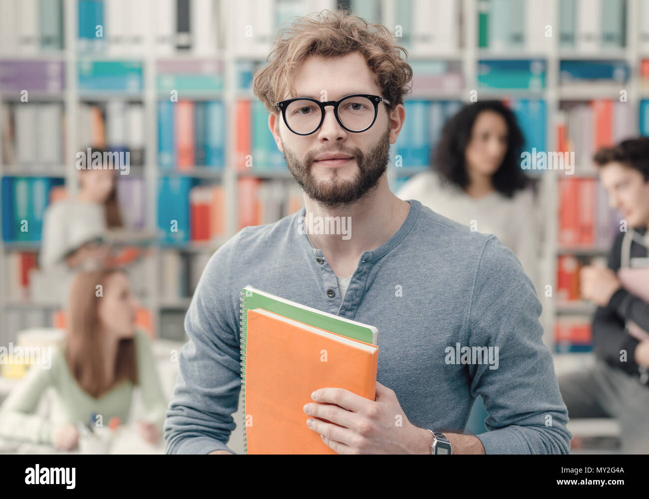 Hipster university student holding notebooks and smiling, students on the background - Stock Image