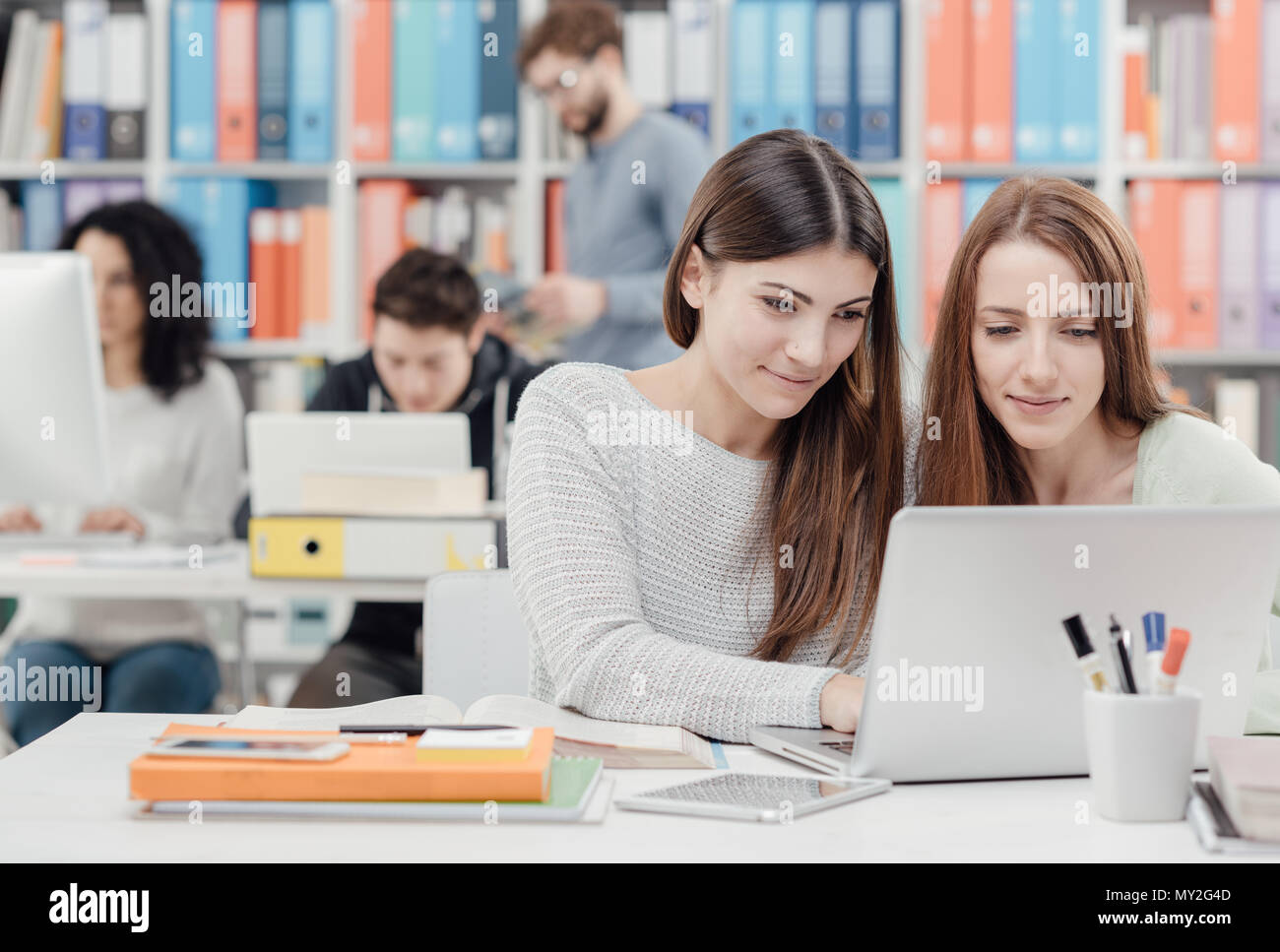 Young female students at the library, they are studying together and connecting with a laptop - Stock Image