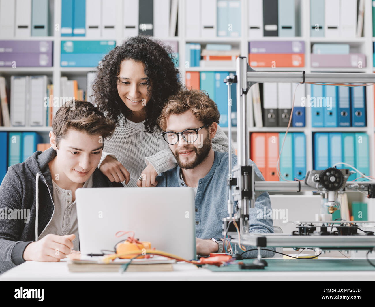 Group of engineering students using a 3D printer and a laptop in the laboratory, technology and learning concept - Stock Image
