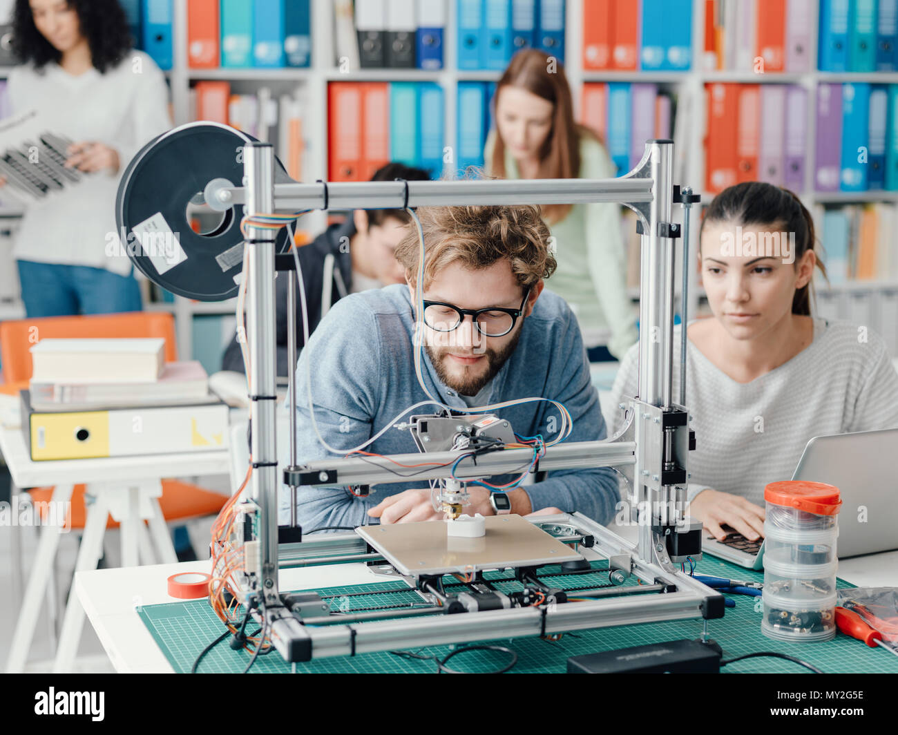 Male and female engineering students using a 3D printer in the lab, technology and learning concept - Stock Image