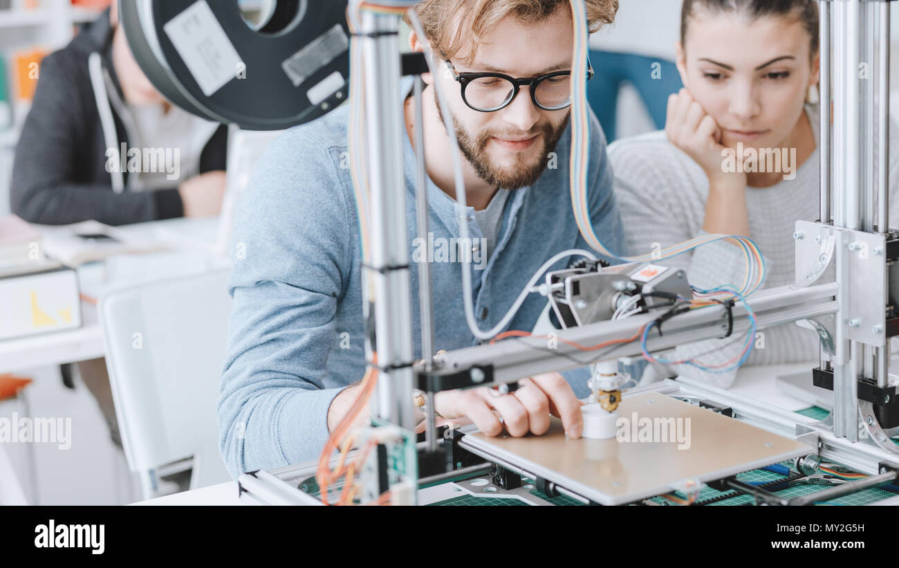 Engineering students using a 3D printer in the lab, learning and technology concept - Stock Image