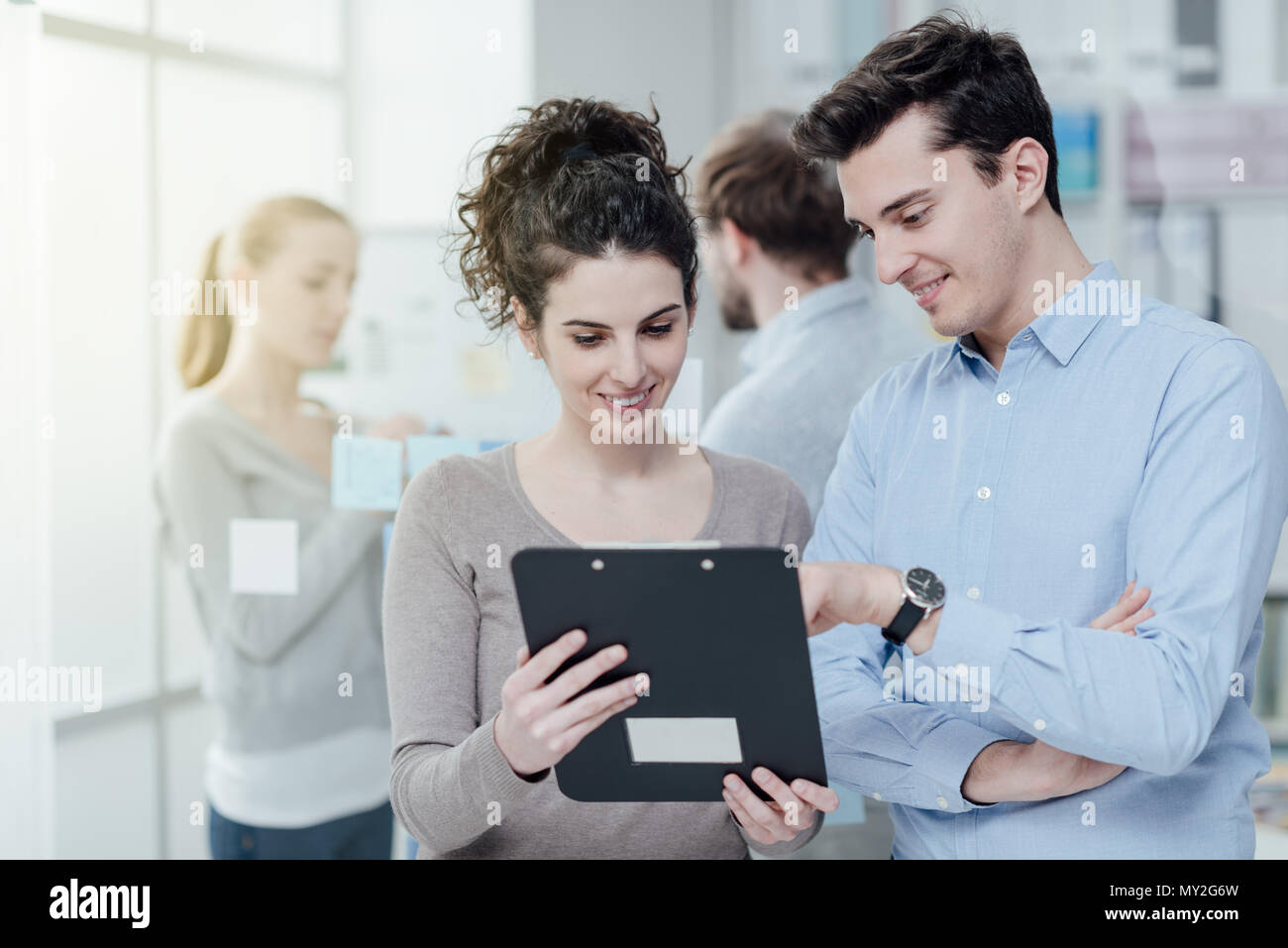 Young confident business people posing in the office and smiling at camera, the woman is holding a clipboard and showing a report to his colleague - Stock Image