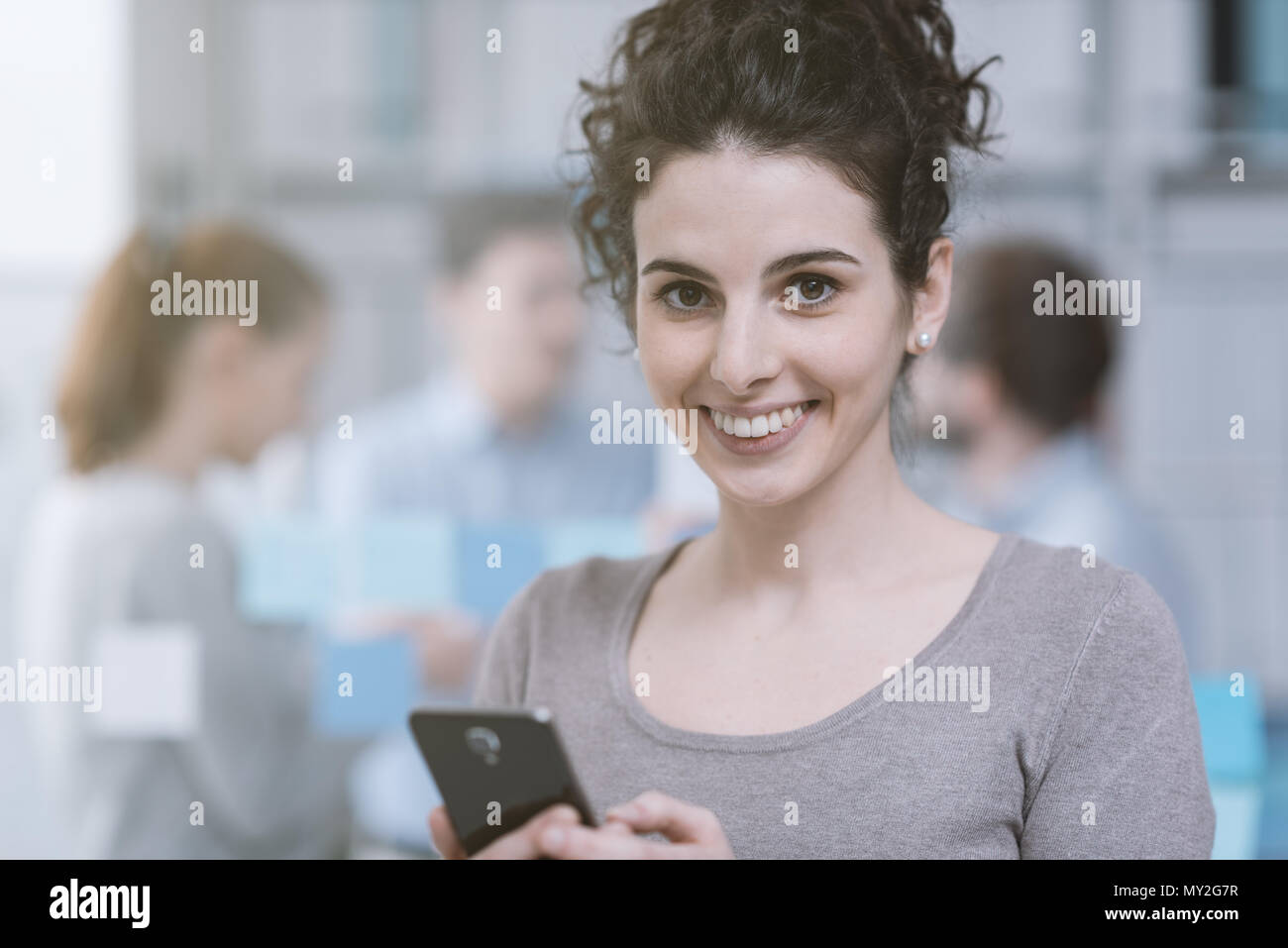 Young smiling woman connecting with her smartphone in the office and business people on the background - Stock Image