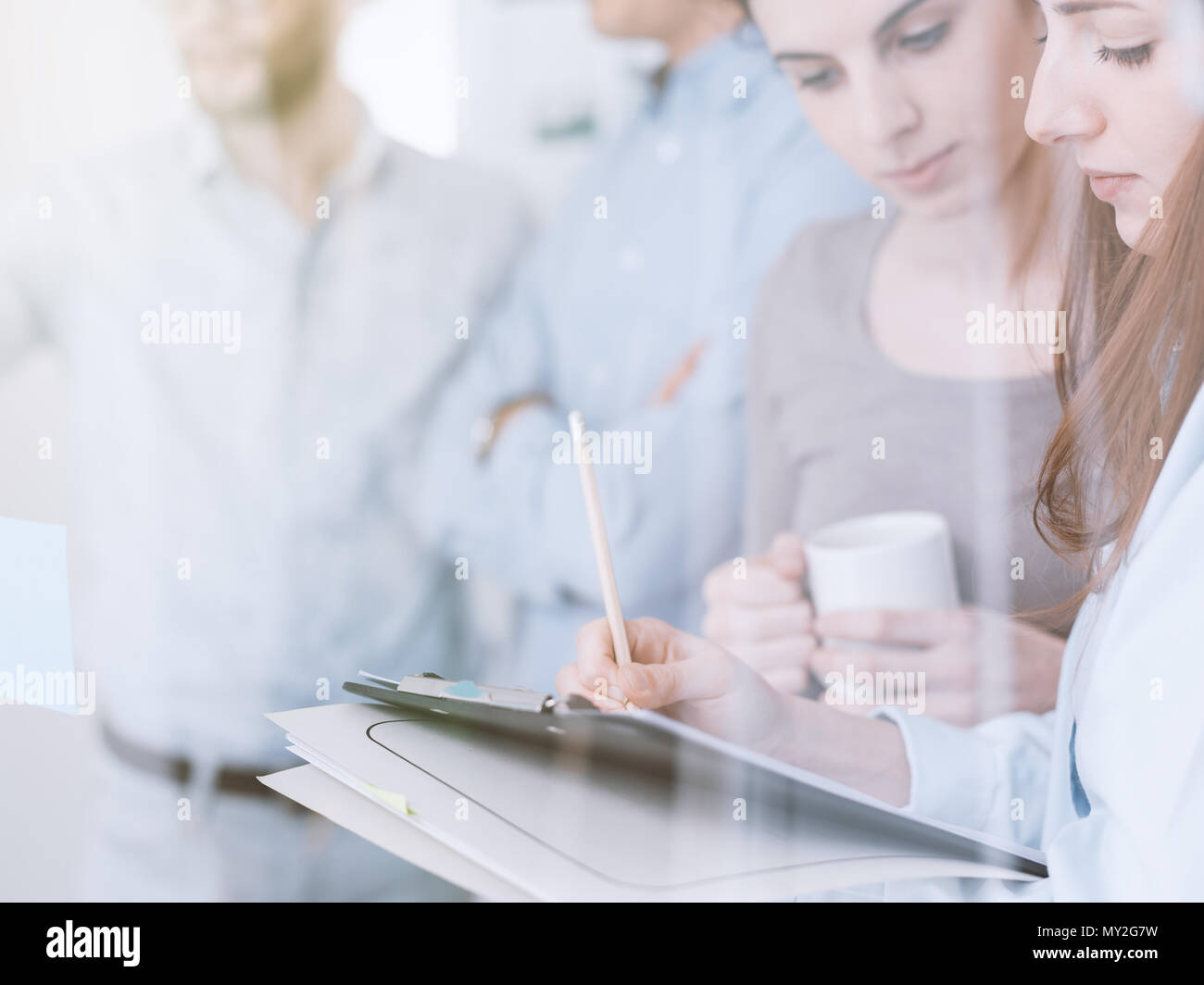 Young business team working in the office, two women on the foreground are checking paperwork on a clipboard - Stock Image