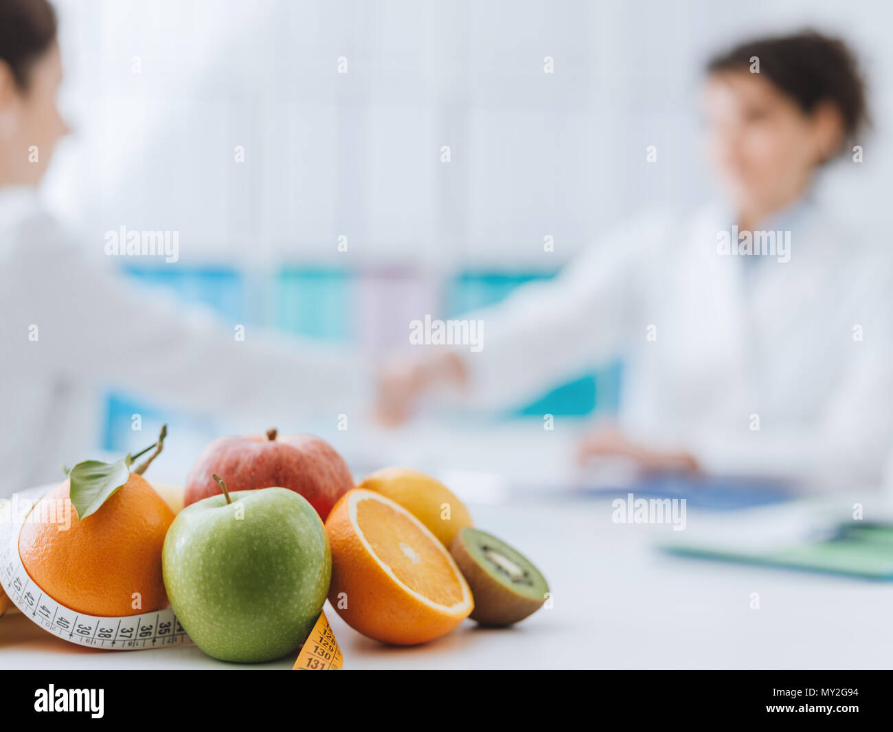 Professional nutritionist meeting a patient in the office and healthy fruits with tape measure on the foreground: healthy eating and diet concept - Stock Image