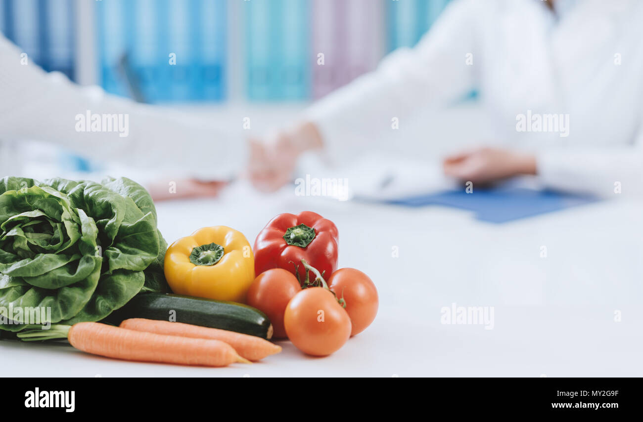 Professional nutritionist working in the office and healthy fresh vegetables on the foreground: diet and health concept - Stock Image