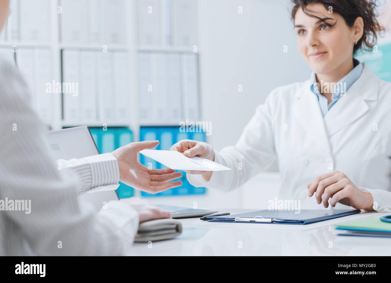 Doctor and patient meeting in the office, the doctor is giving a prescription and a medical report to a woman - Stock Image