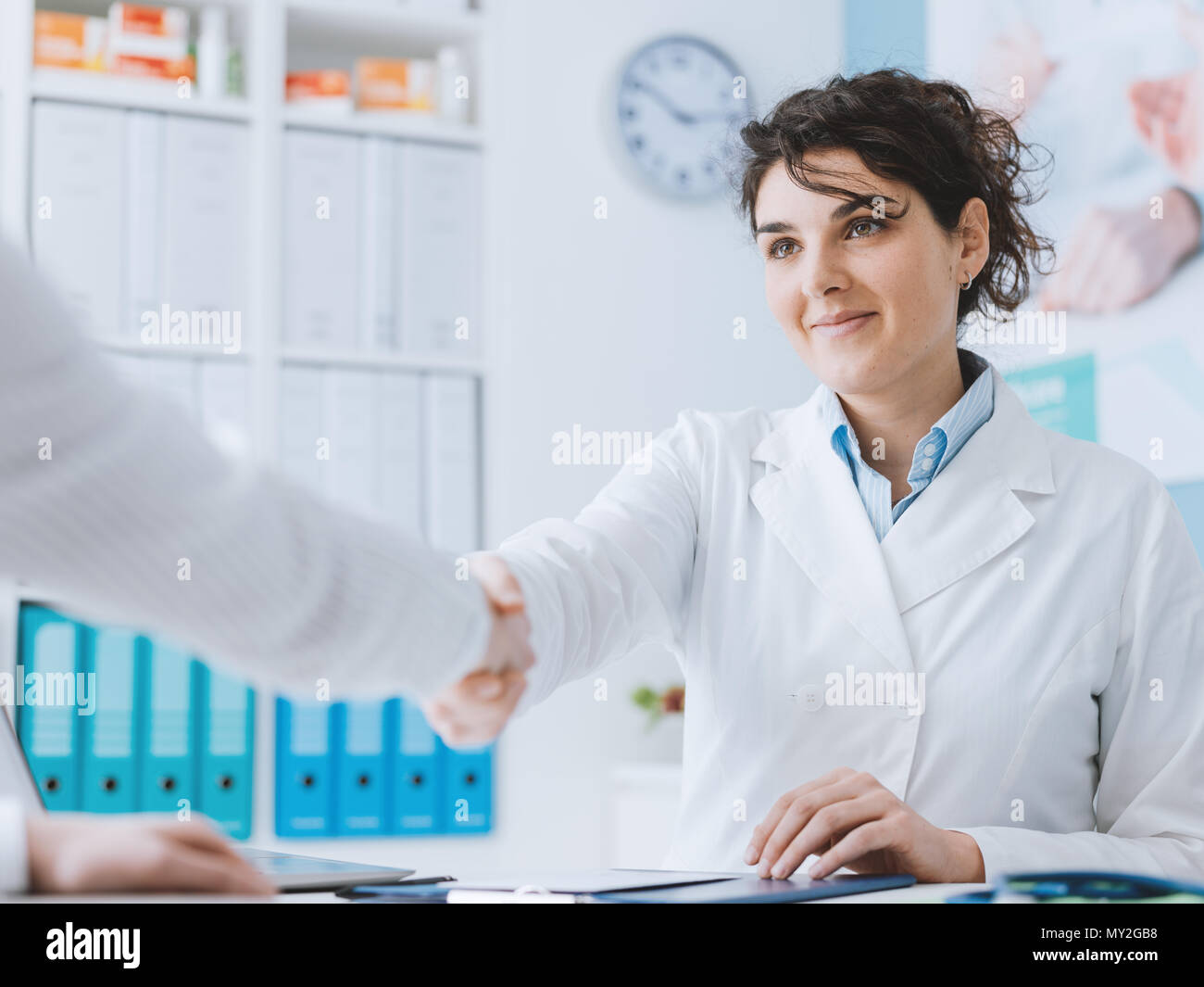 Smiling female doctor greeting a patient and shaking hands, they are having a meeting in the office - Stock Image
