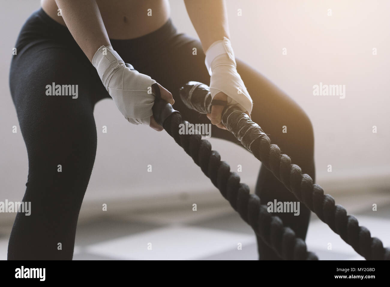 Young sporty woman doing battle rope training, she is swinging the rope, hands close up - Stock Image