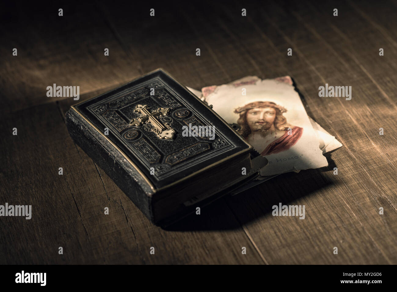 Sacred bible and Holy card with Jesus Christ image on a wooden desk, religion and faith concept - Stock Image