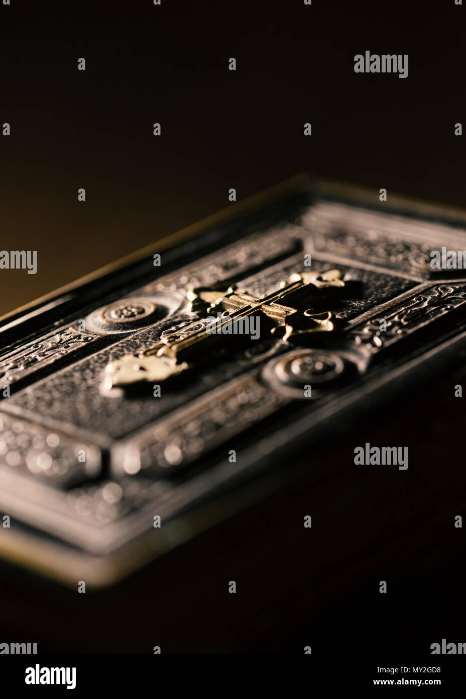Precious antique Bible with golden cross close up, religion and spirituality concept - Stock Image