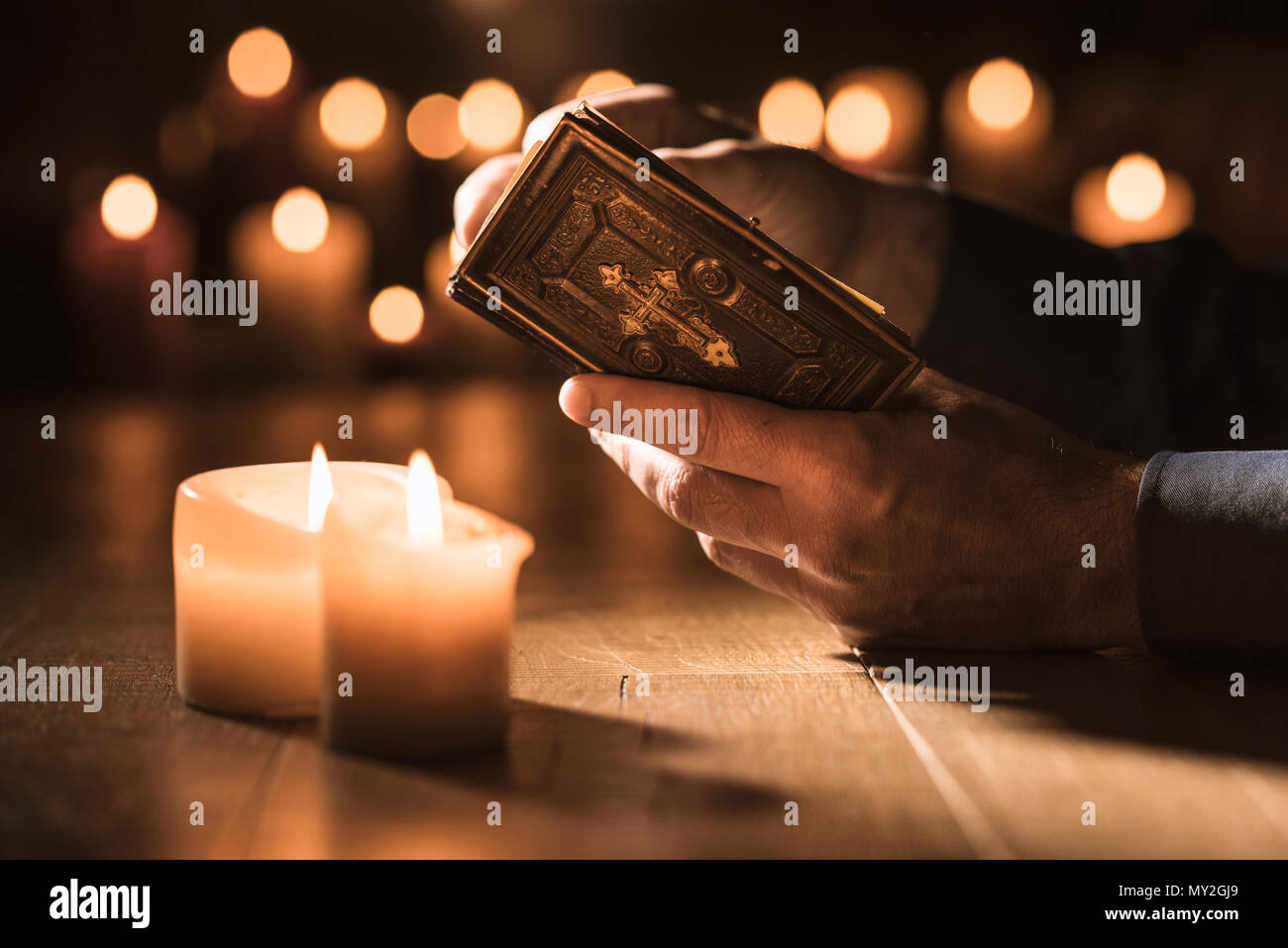 Religious man reading the Holy Bible and praying in the Church with lit candles, religion and faith concept - Stock Image