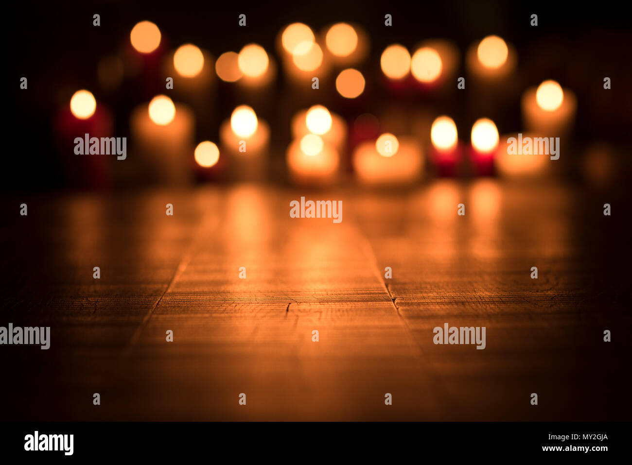 Defocused lit candles burning in the Church, spirituality and religion concept - Stock Image