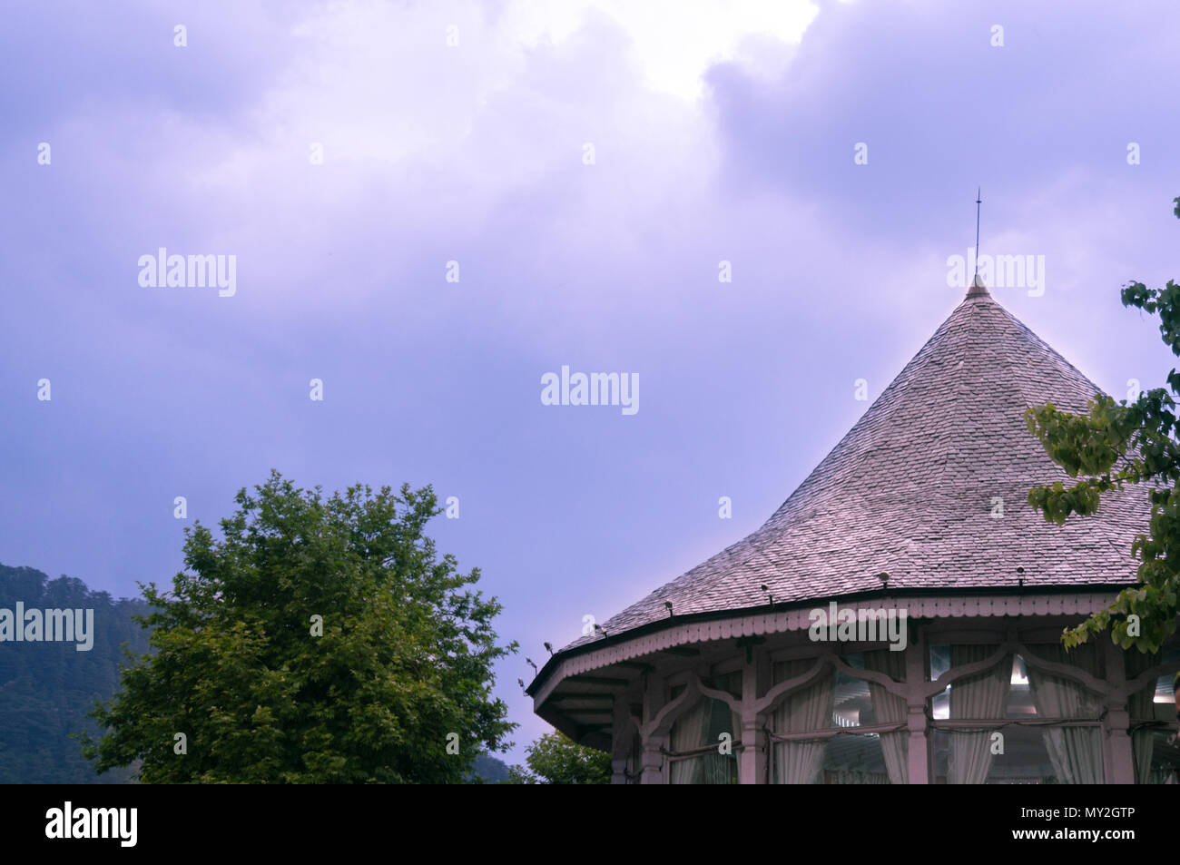 Round building with a conical roof made of bricks shot against a cloudy sky during the evening. Common feature in the buildings of shimla, darjeeling and other hill stations - Stock Image