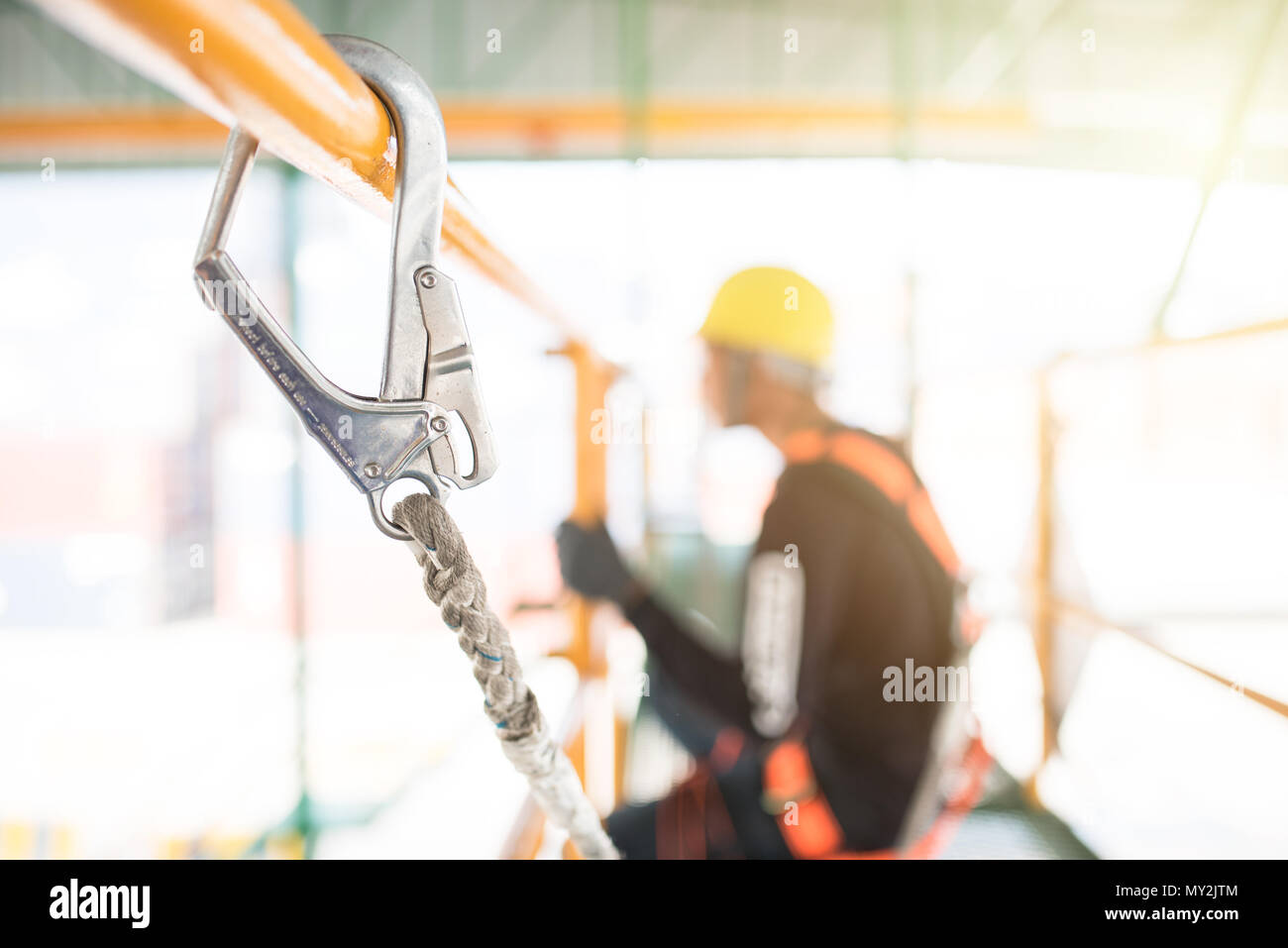Industrial Worker with safety protective equipment loop hanging on the bar besides, safety concept - Stock Image