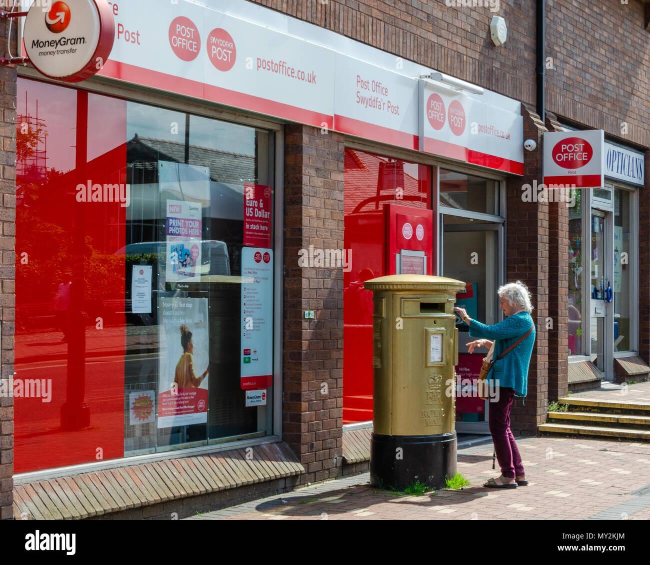 Flint, UK: June 4, 2018: An elderly woman posts some letters in a post box outside Flint Post Office. Stock Photo