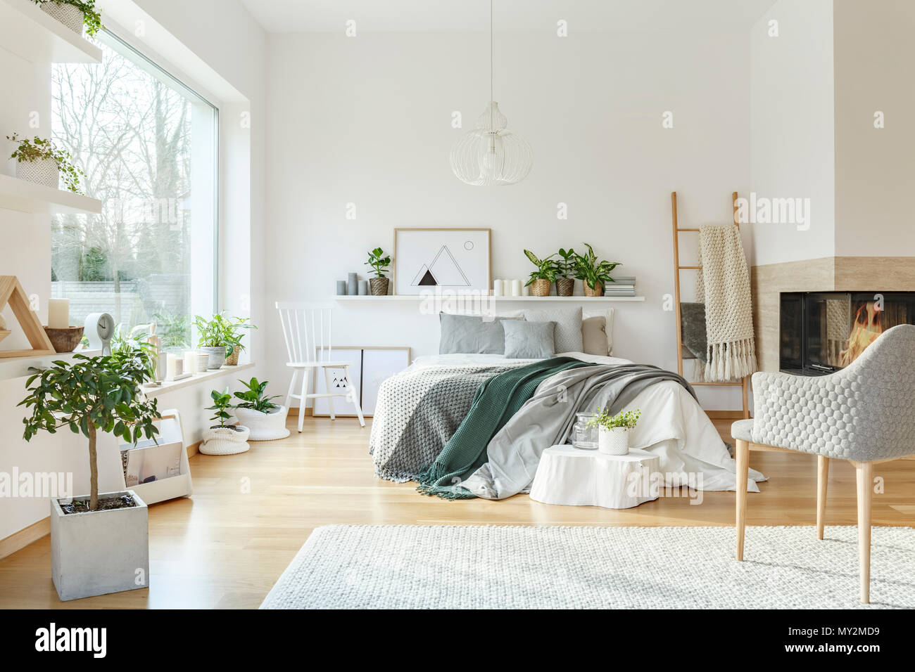 Plant and white armchair in cozy bedroom interior with green ...