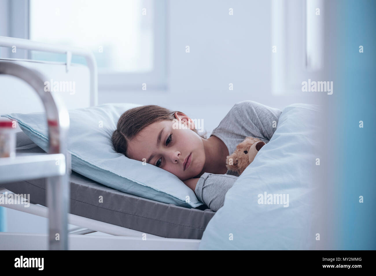 Sad and weak girl lying alone in the hospital bed